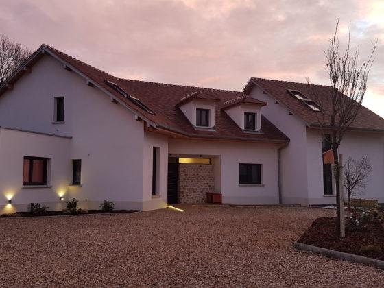 Photo de la construction d'une maison moderne qui mêle tradition avec les pierres et moderne avec les grandes ouvertures et l'acier