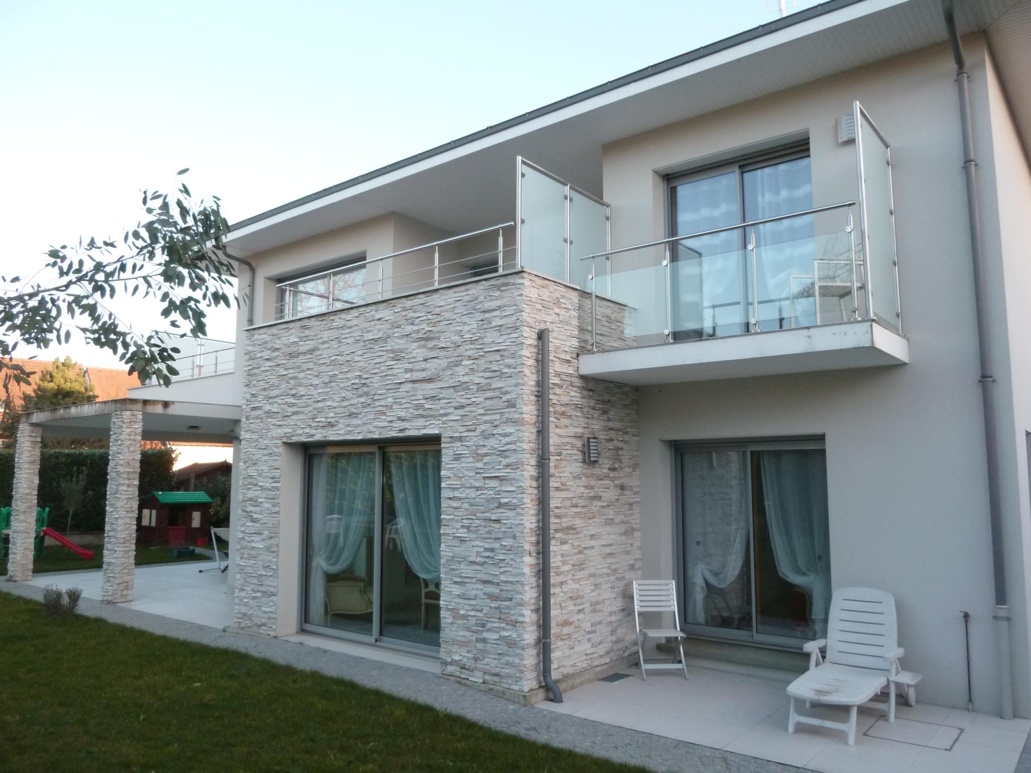 Photo de la maison contemporaine vue du jardin avec ses grands volumes et baies vitrées