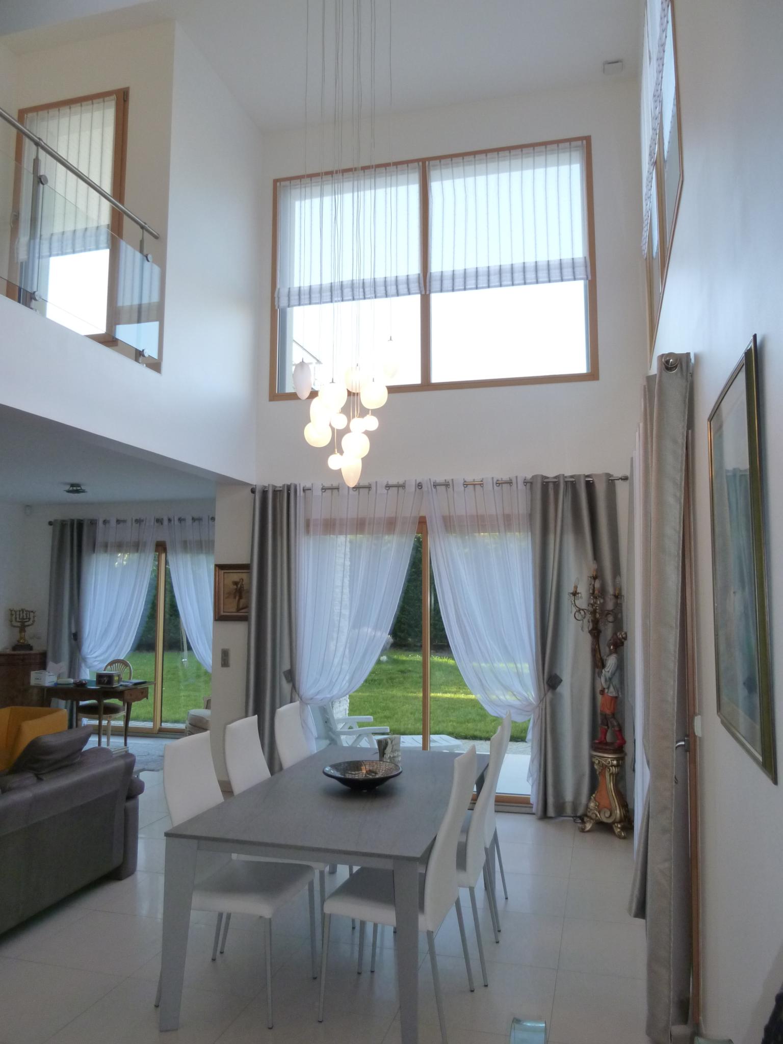 Photo couleur de l'intérieur du salon de la maison contemporaine avec des voilages blanc sur les baies vitrées