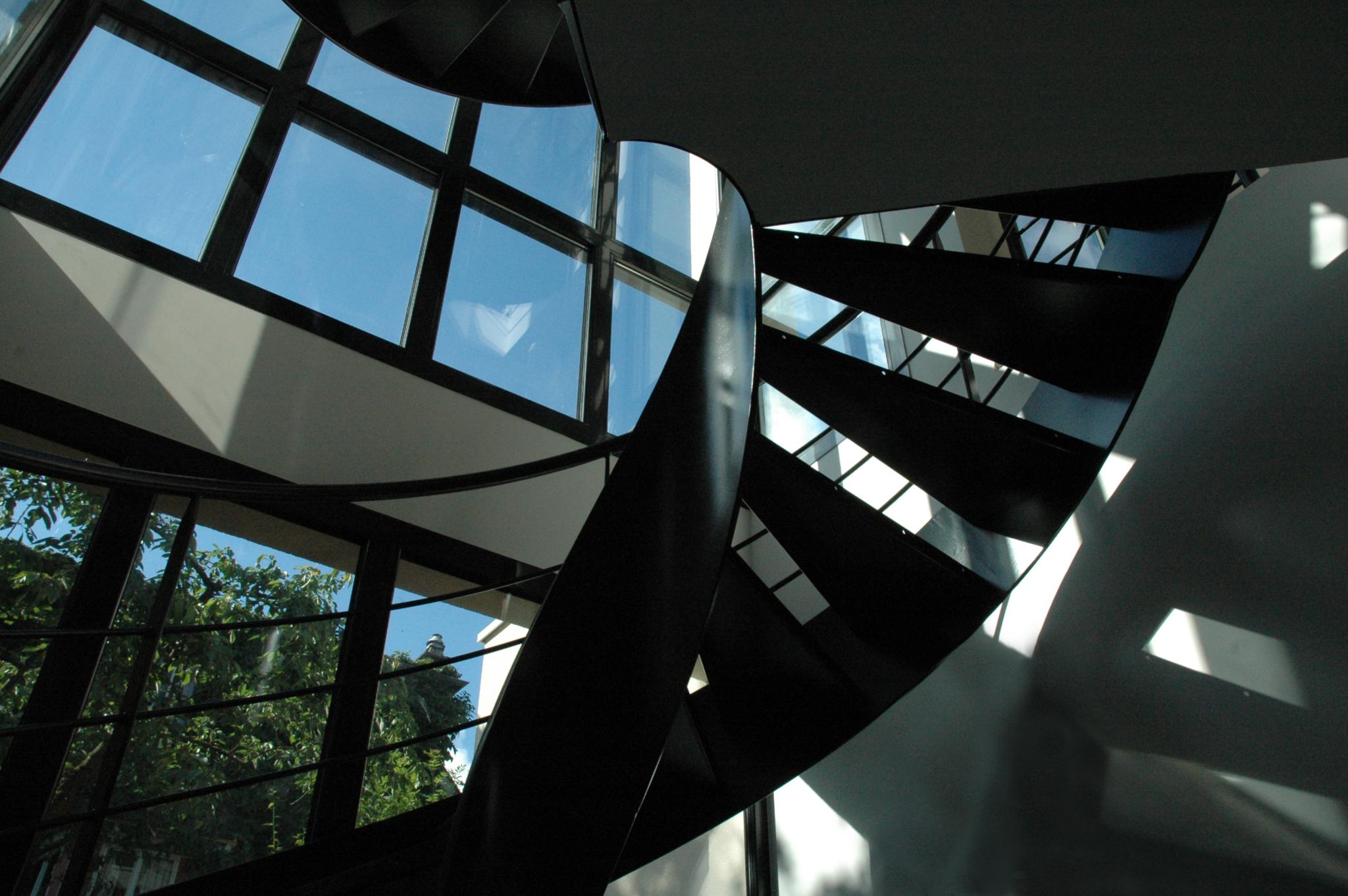 Photo vue d'en dessous d'un escalier en colimaçons avec vue sur l'extérieur avec le ciel dégagé