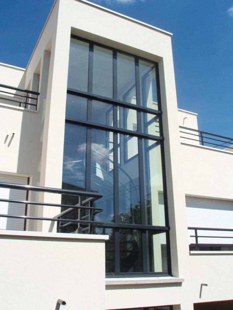 Photo de l'extérieur de la grande ouverture lumineuse de cette maison design très haute rectangulaire qui laisse passer toute la lumière sur l'escalier intérieur